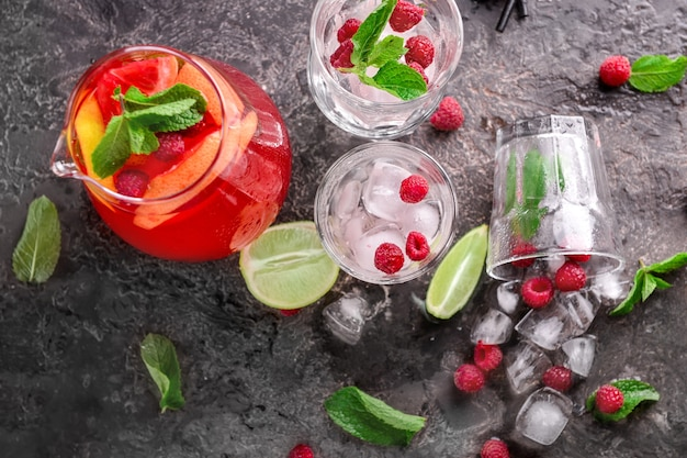 水差しと灰色のテーブルに角氷とグラスで新鮮な夏のカクテル
