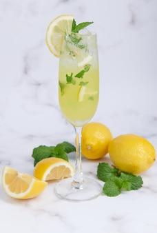 Cocktail estivo fresco con limoni, menta e ghiaccio, immagine di messa a fuoco selettiva, mojito in una tazza di vetro, limonata di agrumi freschi con lime e limoni. bevanda fresca e fresca per il concetto estivo.