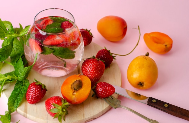 Fresh summer drink with strawberry and mint on pink background