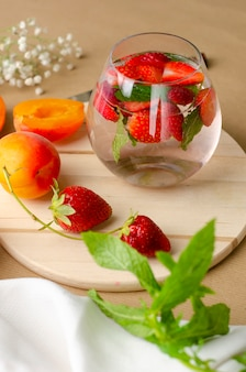 Fresh summer drink with strawberry and mint on wooden board.