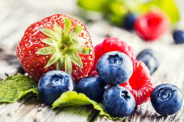 新鮮な夏のフルーツ:おいしいイチゴ、香りのよいグリーンミントの上にブルーベリーを置いた素敵なラズベリー。