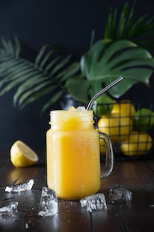 Fresh summer fruits juice with lemon on dark tropical background. close up.