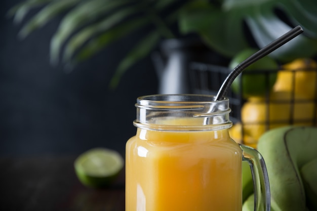 Fresh summer fruits juice with lemon, lime on dark table.