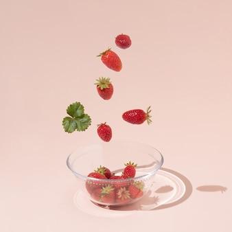 Свежие летние фрукты, клубника и зеленые листья падают в стеклянную миску, изолированную на розовом фоне. креативный макет еды. квадратный