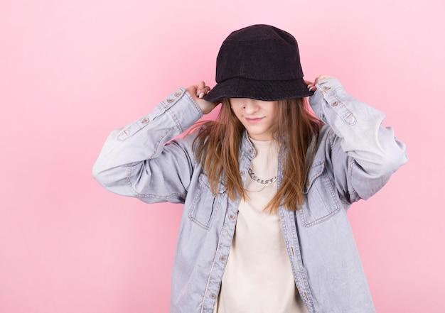 Свежая летняя девушка в джинсовой рубашке и черной панаме. партия монохромный ванильный стиль. минимальные дизайнерские тенденции