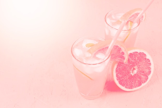 Fresh summer healthy diet beverage and grapefruit on pink background