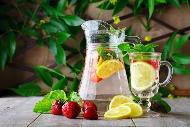Fresh summer healthy drink with lemon and strawberries with ice.