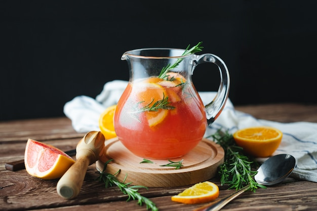 Fresh summer lemonade with grapefruit and rosemary on an old wooden table. summer concept.