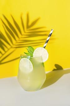 Свежий летний лимонад с лимоном, лаймом, апельсином и мятой на желтом фоне