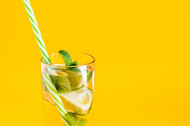 Fresh summer lemonade with water, lime and mint with a straw