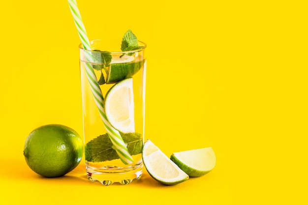 Fresh summer lemonade with water, lime slices and mint in a glass tumbler with a straw on a yellow background. cold, refreshing summer cocktail. fresh drink composition with copy space