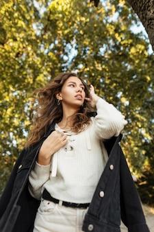 검은색 진 재킷과 니트 블라우스가 있는 패션 가을 데님 옷에 곱슬머리를 한 아름다운 젊은 여성의 신선한 여름 초상화가 야외에서 산책합니다. 캐주얼한 여성스러운 스타일