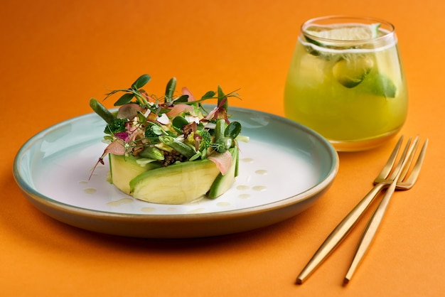 アボカド、ブロッコリー、若い豆のオレンジ色の背景の新鮮な夏のサラダ