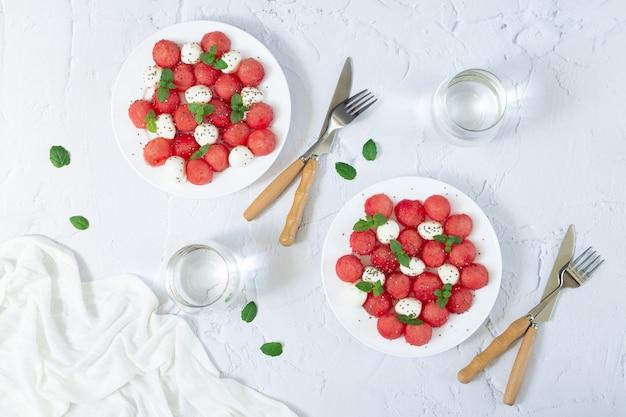 スイカ、ミニモッツァレラチーズ、ミントの葉、チアシードの新鮮な夏のサラダ。健康的なベジタリアンダイエットのコンセプト