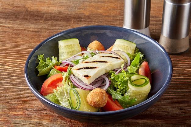 新鮮な夏のベジタリアンサラダ、トマトほうれん草とロースト豆腐チーズを木製のバックのプレートに入れて...
