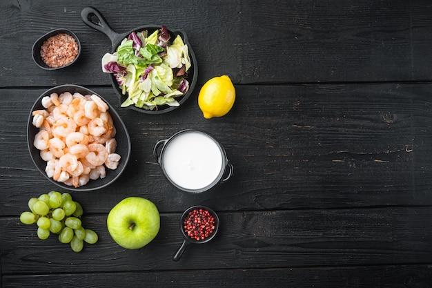 Свежая летняя витаминная закуска из зеленого салата, креветок, оливковых ингредиентов, с соусом из яблок и винограда, на черном деревянном столе, плоская планировка, вид сверху