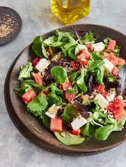 オリーブオイルと種をまとった、フェタチーズと緑の葉の新鮮な夏のスイカのサラダ