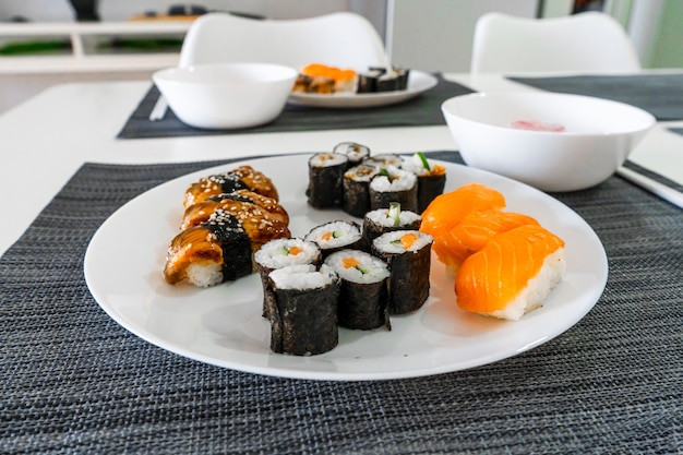 Свежие суши и роллы в белой тарелке. суши-ланч.