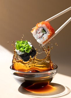 Свежий суши-ролл, падающий в блюдо с соевым соусом с брызгами жидкости в замораживающем движении. левитация, копировать пространство