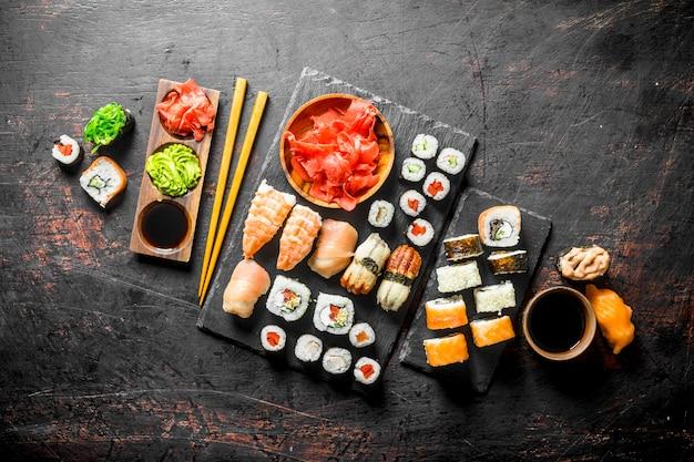 Свежие суши-роллы на черной каменной подставке на черном деревенском столе