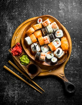 Fresh sushi rolls in a plate on a cutting board with chopsticks and sauces. on dark rustic