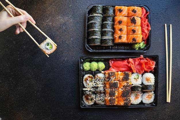 Свежие суши роллы с лососем, рыбой, рисом и нори на столе