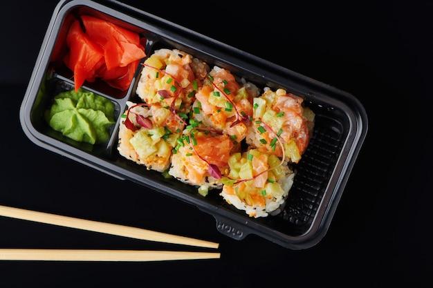 새우를 곁들인 신선한 스시 롤, 테이크아웃을 위해 도시락에 제공되는 게. 건강한 점심을 위해 일본 스시 음식 컨셉으로 이동합니다. 검은 배경에 근접 촬영 상위 뷰입니다.