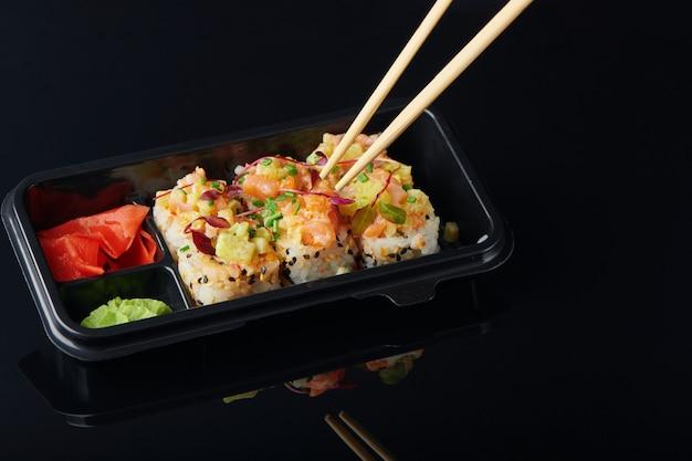 새우를 곁들인 신선한 스시 롤, 테이크아웃을 위해 도시락에 제공되는 게. 건강한 점심을 위해 일본 스시 음식 컨셉으로 이동합니다. 검은 배경에 근접 촬영 보기입니다.