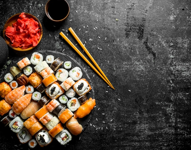 Fresh sushi rolls with vegetables, shrimp and salmon. on dark rustic background