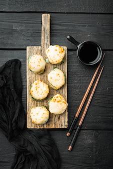 わさびと生姜をセットした新鮮な巻き寿司、黒い木製のテーブル