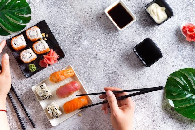 Fresh sushi set on black and white slate, hand hold metal sticks, sauce and green leaves