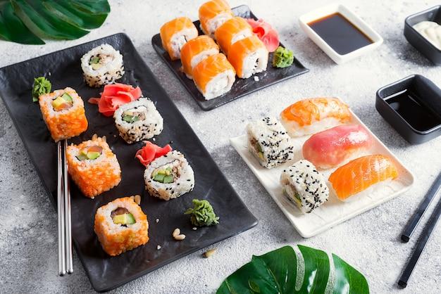 Набор свежих суши на черно-белом сланце с металлическими палочками, соусом и зелеными листьями