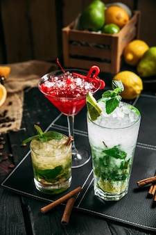 Fresh sweet alcohol cocktails in different glasses, mojito cosmopolitan and mai tai on the dark wooden background, closeup, vertical