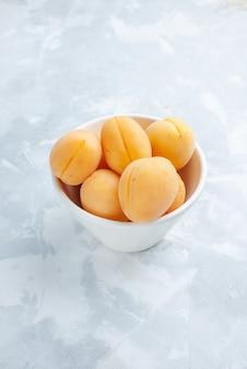 白い机の上のプレートの中に新鮮な甘いアプリコットのまろやかでおいしい果物、果物の新鮮な夏の食べ物の食事のビタミン