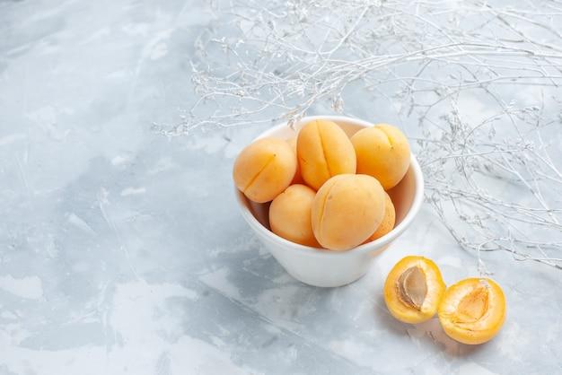新鮮な甘いアプリコットは白い机の上のプレートの中に果物をまろやかにします、果物の新鮮な夏の食べ物の食事のビタミン