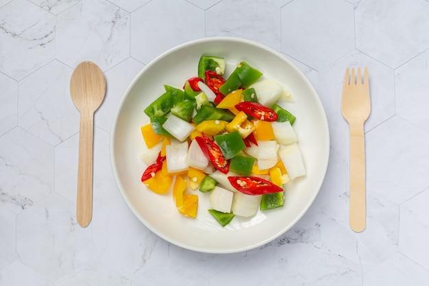 흰색 접시에 신선한 달콤한 피망과 양파 슬라이스
