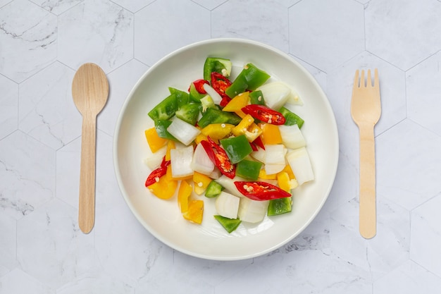Fresh sweet bell pepper and onion sliced on white plate