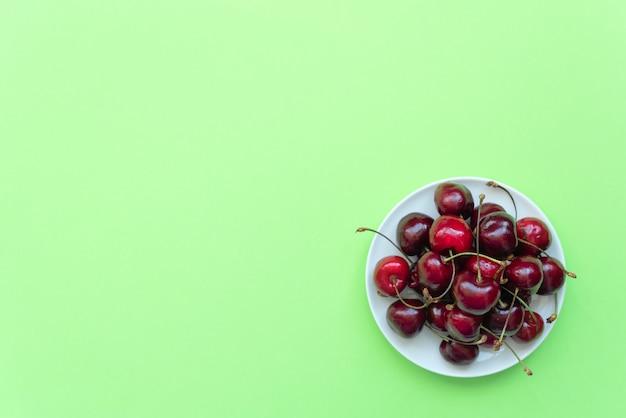 Свежая черешня на белой тарелке на зеленом фоне