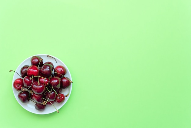 Свежая черешня на белой тарелке на зеленом фоне.