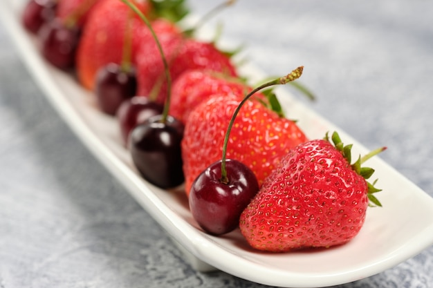Fresh sweet cherries and strawberries on a white plate.