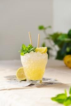 Свежий сладкий коктейль с лимоном, мятой и замороженным льдом на светлом столе, изображение выборочного фокуса