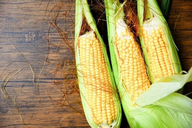Fresh sweet corn ears on wooden