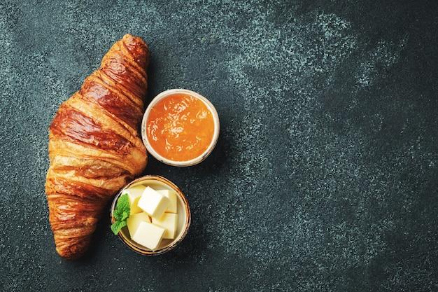 Свежий сладкий круассан с маслом и апельсиновым джемом на завтрак. континентальный завтрак на черном бетонном столе. вид сверху с копией пространства. плоская планировка.