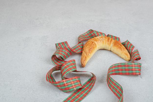 Croissant dolce fresco con fiocco festivo sulla superficie bianca.