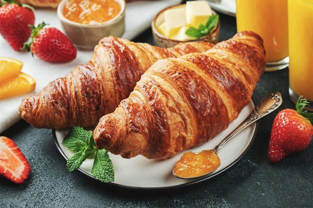 Свежие сладкие круассаны с маслом и апельсиновым джемом на завтрак. континентальный завтрак на темном фоне бетона.