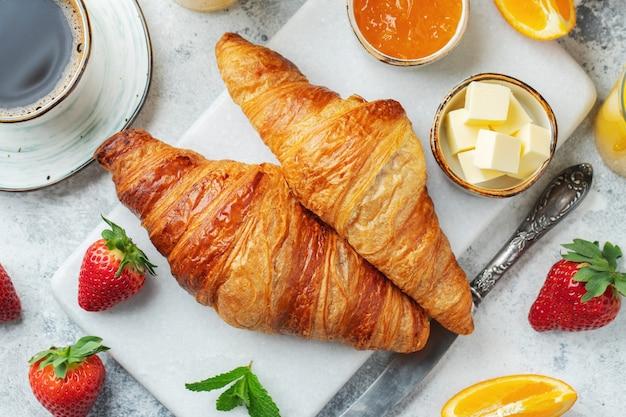 Свежие сладкие круассаны с маслом и апельсиновым джемом на завтрак. континентальный завтрак на белом бетонном столе. вид сверху. плоская планировка.