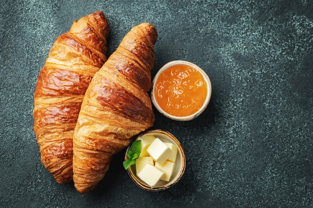Свежие сладкие круассаны с маслом и апельсиновым джемом на завтрак.