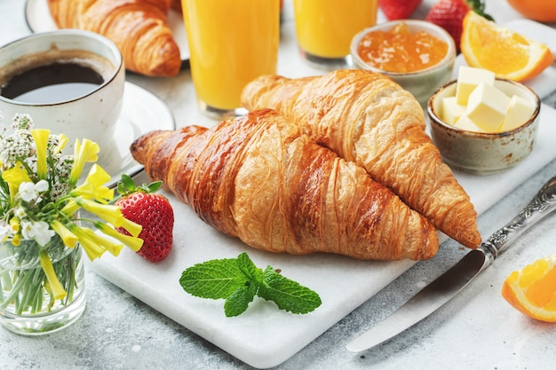 Fresh sweet croissants with butter and orange jam for breakfast.
