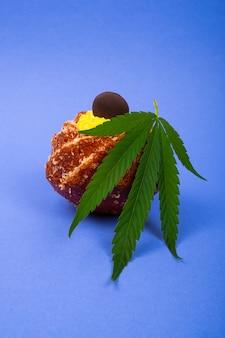 青い背景のクローズアップ、マリファナの植物の葉と新鮮な甘いカップケーキ、大麻、甘いペストリー、デザートとお菓子。