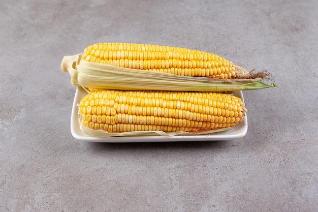 흰 접시에 고립 된 옥수수의 신선한 달콤한 귀